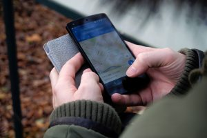 A person holding a phone with the Google Maps app open